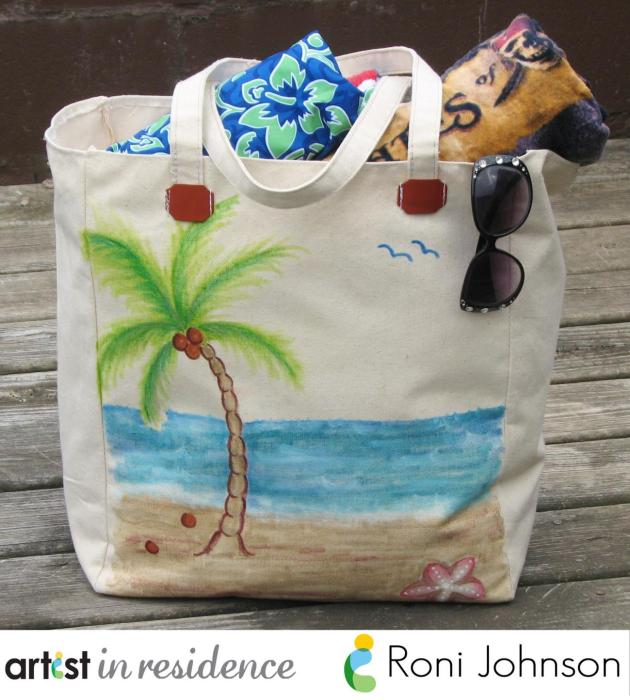 Hand painted with a beach scene including sand, starfish, palm tree with coconuts, the ocean and some flying birds using All-Purpose Inks, a canvas tote is full of supplies ready to head to the beach.