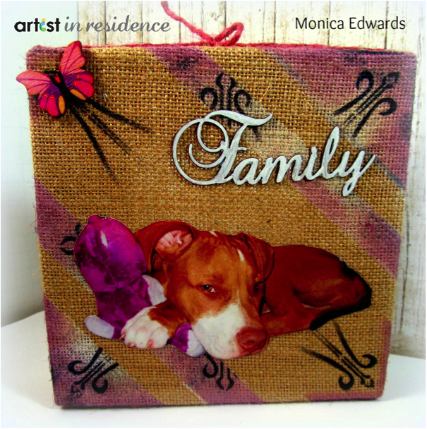 A handmade custom home decor art piece made by inking a stretched burlap canvas with StazOn and Encore Ulitmate Metallic inks with photo of the family dog and the world Family in Silver chipboard.