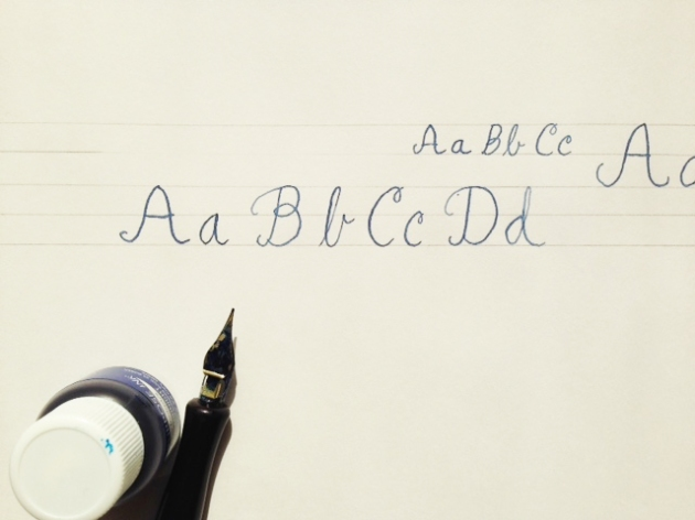 Some hand drawn letter with ink and calligraphy pen sitting nearby.