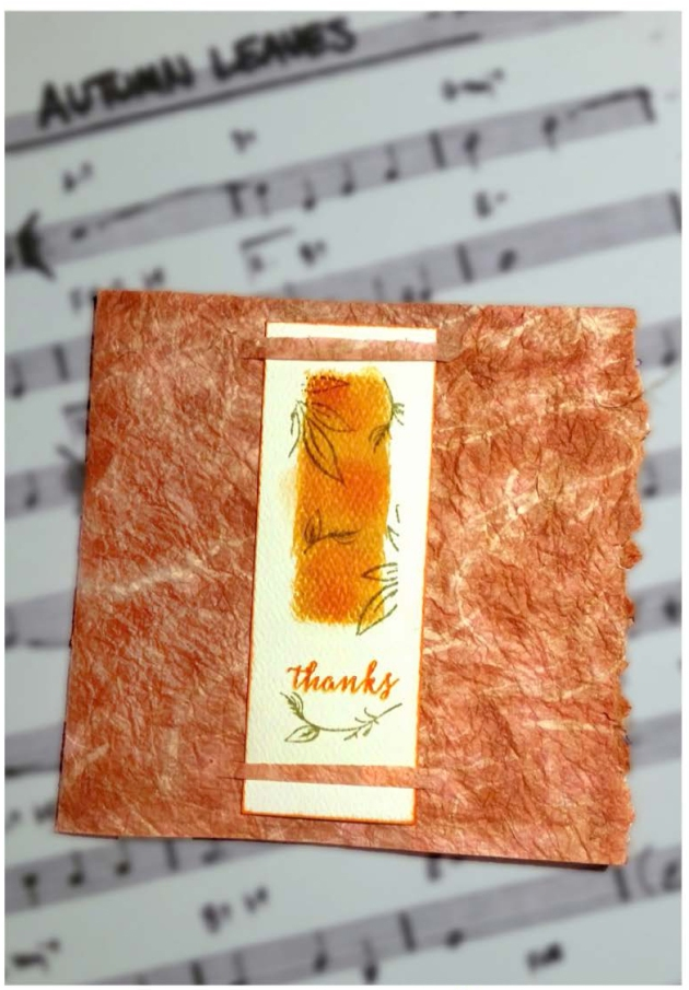An elegant handmade card featuring tea-stained handmade paper and a daubed center piece with Kaleidacolor inks by Mark Melnick.