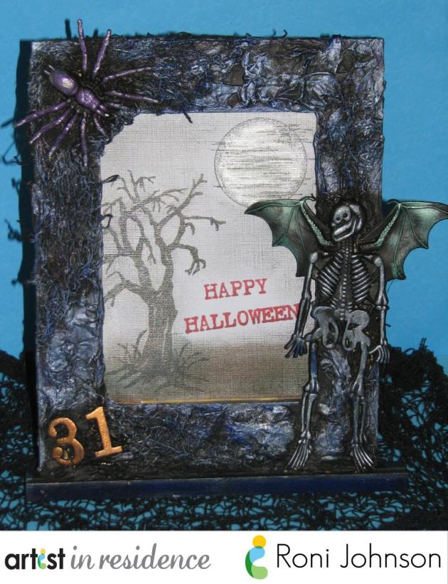 A highly textured blackened Halloween picture frame decorated with plastic embellishments and highlighted with Tsukineko Metallic Inks by Roni Johnson.