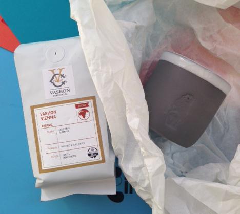 A bag of coffee and a handmade handleless mug.