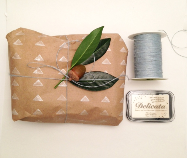 A handmade package of stamped butcher paper wiht a grennery topping and Delicata White Shimmer ink with the roll of twine used in creating the gift.