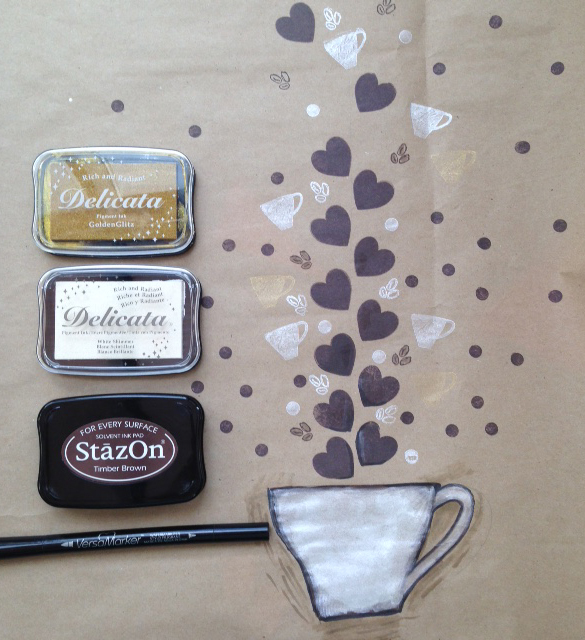 A handdrawn coffee cup and stamped elements on kraft butcher paper with the Delicata, StazOn and VersaMarker inks used to make it.