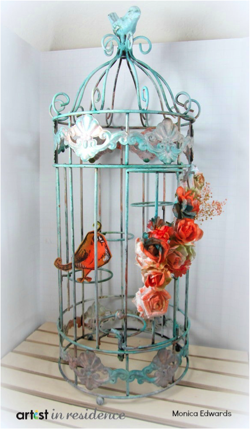 Altered birdcage featuring flowers and bird colored with Fireworks! Sprays by Monica Edwards.