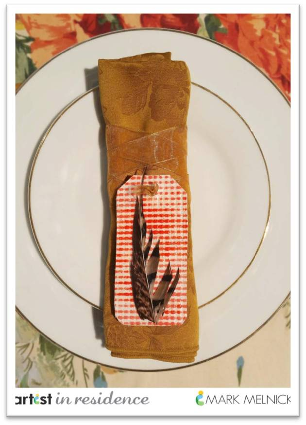 A uniuqe tag style napkin ring featuring textured paper and a pheasant feather by Mark Melnick.