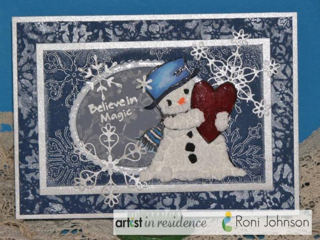 """A handmade snow centric card featuring many blue and sparkly layers of snowflakes and a snowman made with Radiant Neon Amplify! and the sentiment """"Believe in Magic"""" made by Roni Johnson."""