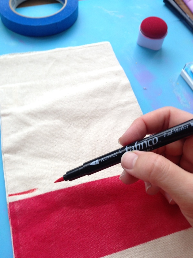 Drawing on a muslin gift bag with a Fabrico Marker above a big red blog created by VersaCraft.