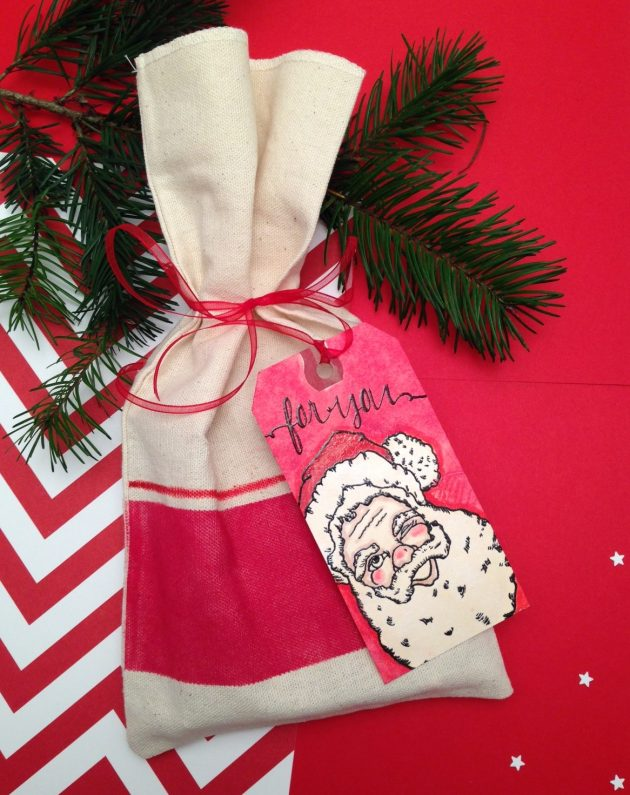 A handmade gift bag inked in Poppy Red block and stripe with a handmade tag featuring Santa Clause.