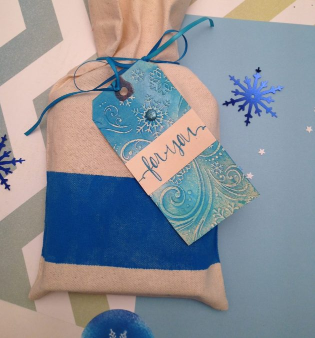 A muslin giftbag inked with Ultramarine VersaCraft in a block section with a handmade tag embossed with a snowflake pattern and inked in blue too.