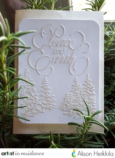 "Subtle yet elegant white on white holiday card handmade by Alison Heikkila featuring the sentiment ""Peace on Earth"" made with Creative Medium through a stencil."