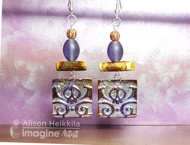 Alison Heikkila embosses Sheet Metal and creates earrings. purple, yellow, beads, skull, diy, jewelry.