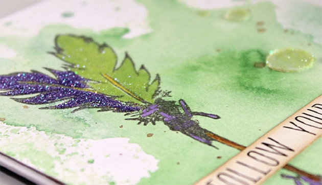 Jowilina Nolte creates a Follow Your Hear encouragement card with On Point Glue, Memento and glitter. green, purple, glam, arrows, feathers, embellishments, bronze brad.