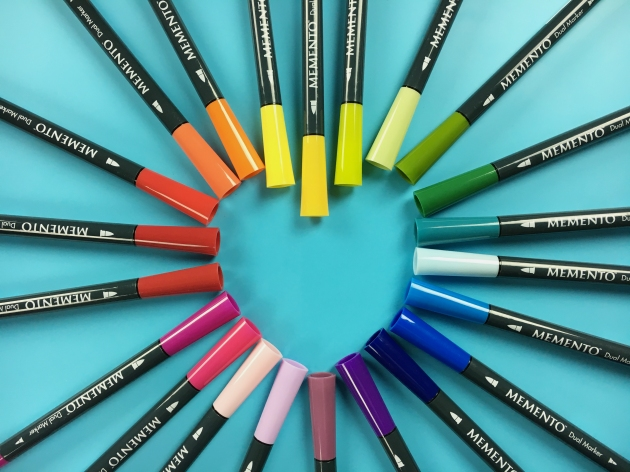 Several colors of Tsukineko's Memento Dual Tip Markers deisplayed with the caps making the shape of a heart.