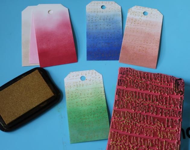 Gift tags blended with colorful Delicata inks in red, green, blue and rose gold overstamped with a musical sheet stamp in Delicata Gold.