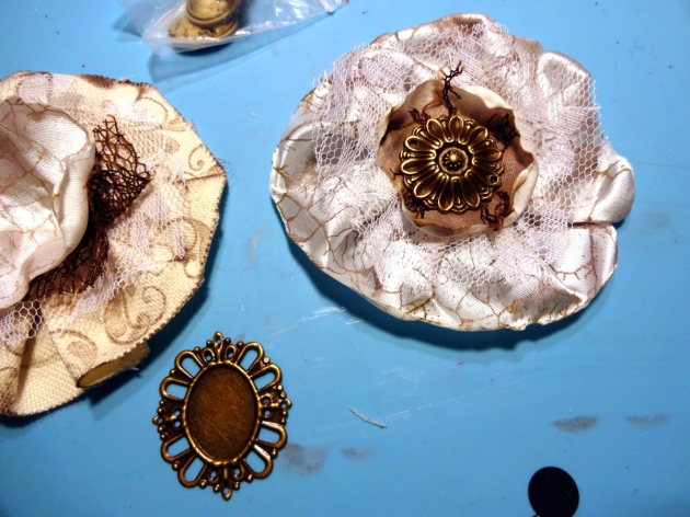 Make layers of lace and fabric by gluing to the center of the rosettes. Decorate with cameo and metallic embellishments.