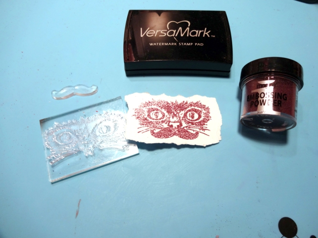 VersaMark and Imagine Embossing Powder in Vintage Plum to stamp the cat stamp on a distressed edges piece of cardstock