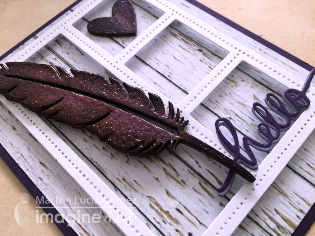 "Close up of a handmade card featuring a shiny embossed wooden feather and the sentiment ""hello"" inked in purples with Memento Luxe ink by Martha Lucia Gomez."