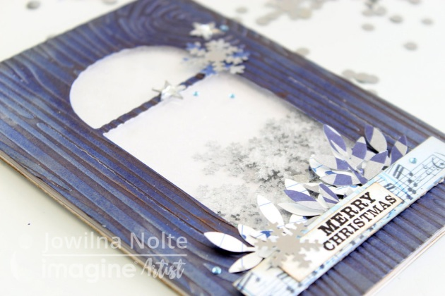 Close up of a handmade Christmas shaker card featuring a wood grain embossed panel, silver snowflake confetti and Delicata Sapphire Blue and Dark Brown Shimmer.