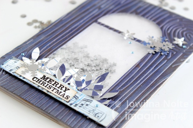 Details of a handmade Christmas shaker card featuring a wood grain embossed panel, silver snowflake confetti and Delicata Sapphire Blue and Dark Brown Shimmer.