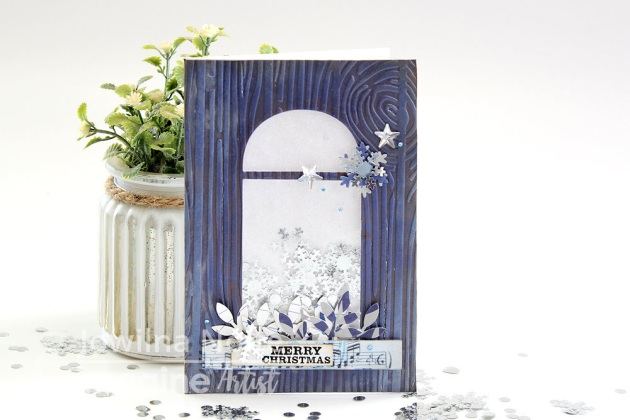 Handmade Christmas shaker card featuring a wood grain embossed panel, silver snowflake confetti and Delicata Sapphire Blue and Dark Brown Shimmer.