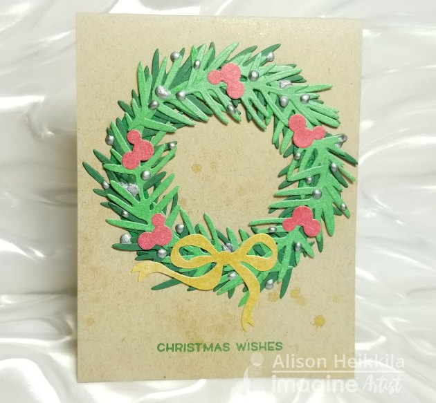 "the card with a simple ""Christmas Wishes"" sentiment from Lawn Fawn stamped in Delicata Emerald Green and by adding ""ornaments"" with Silver Irresistible Pico Embellisher"