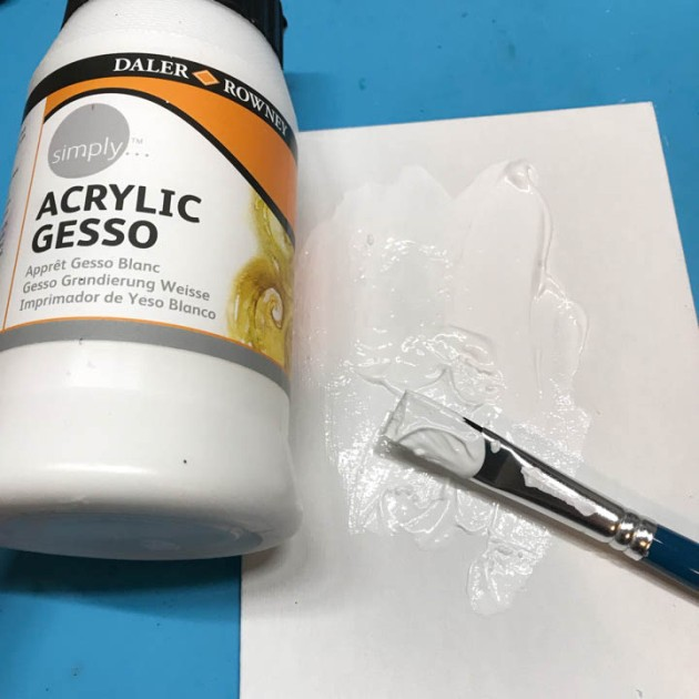 Gesso applied to a canvas with a flat tipped brush.